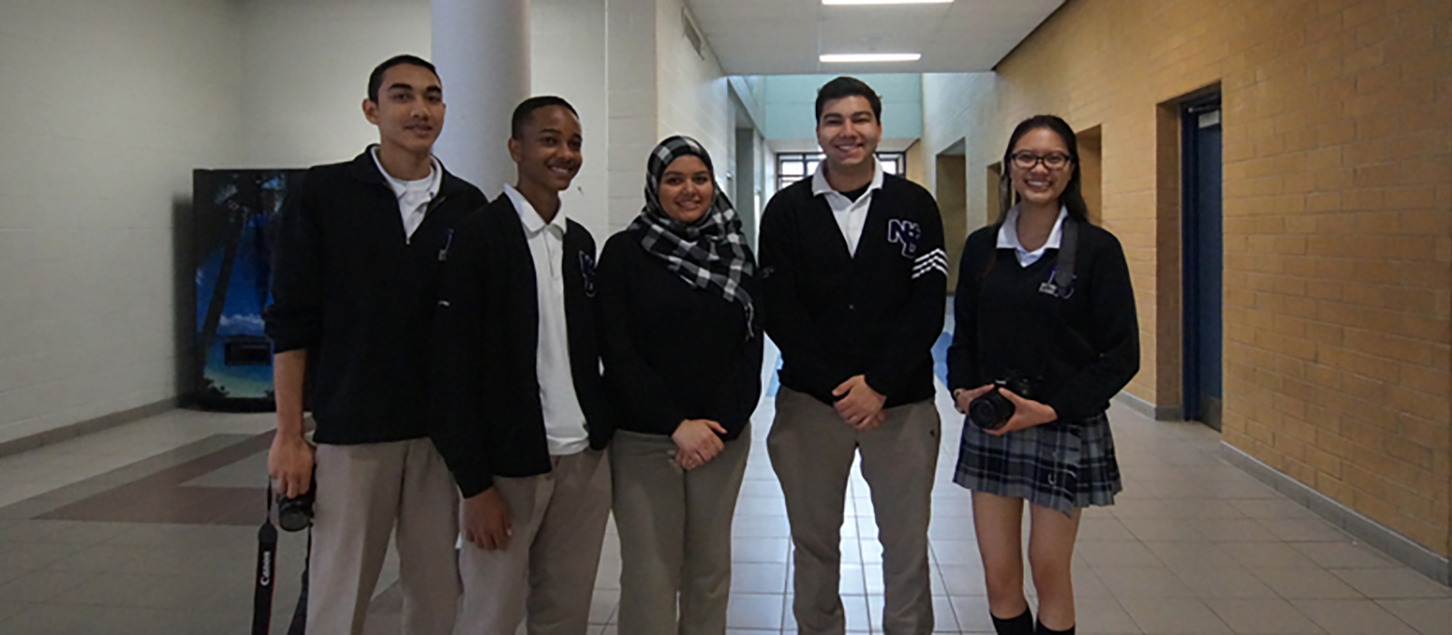 Male and female student leaders standing in a hallway